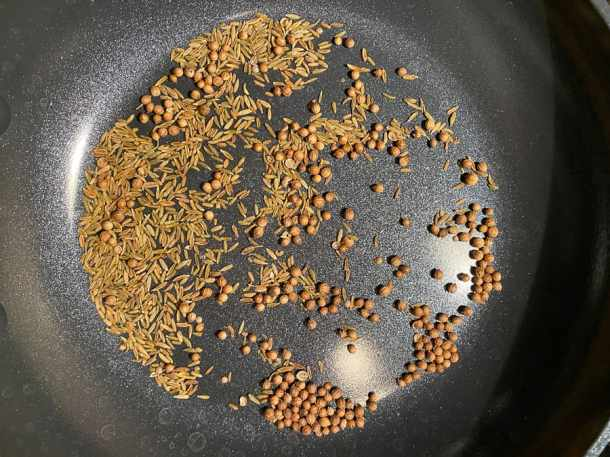 coriander seeds and cumin seeds toasting in a pan