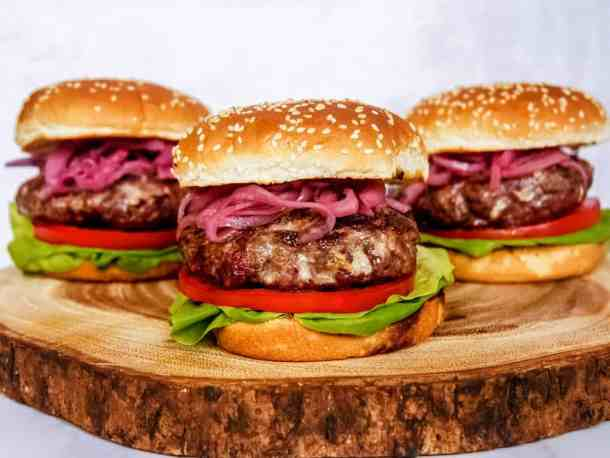 front shot of three blue cheese burgers next to each other garnished with pickled red onions, sliced tomatoes, and lettuce on a wooden block