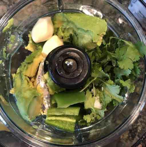 overhead shot of cilantro, jalapeno, avocado, garlic in a food processor unblended