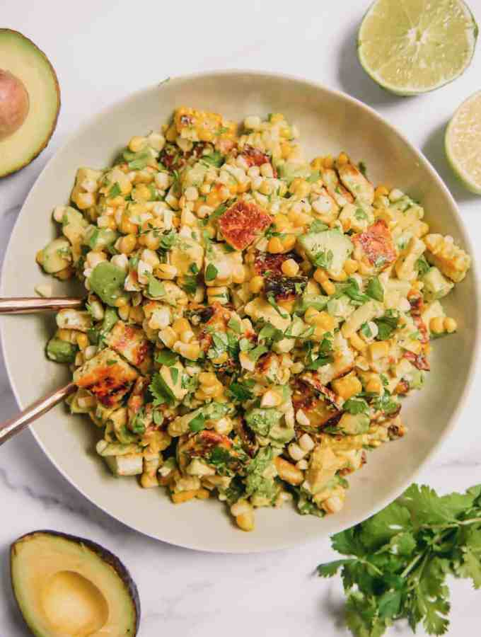 grilled halloumi, avocado, and corn, mixed together in a bowl with cilantro and whole avocados surrounding