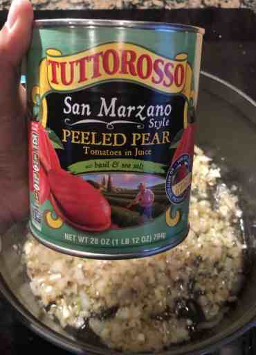 can of san marzano tomatoes in front of dutch oven