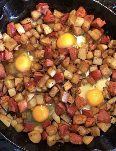 diced potatoes and chorizo in a cast iron skillet with four uncooked eggs cracked on top