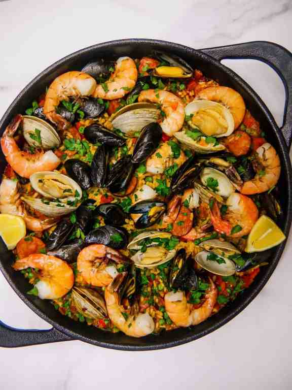overhead photo of seafood and chorizo paella with shrimp, mussels, clams, in a cast iron skillet