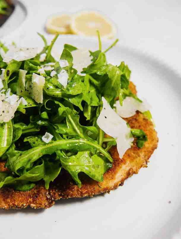 close up front shot of chicken milanese with arugula piled on top and fresh parmesan