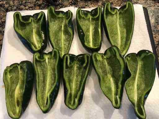 poblano peppers hollow and cut in half on a paper towel