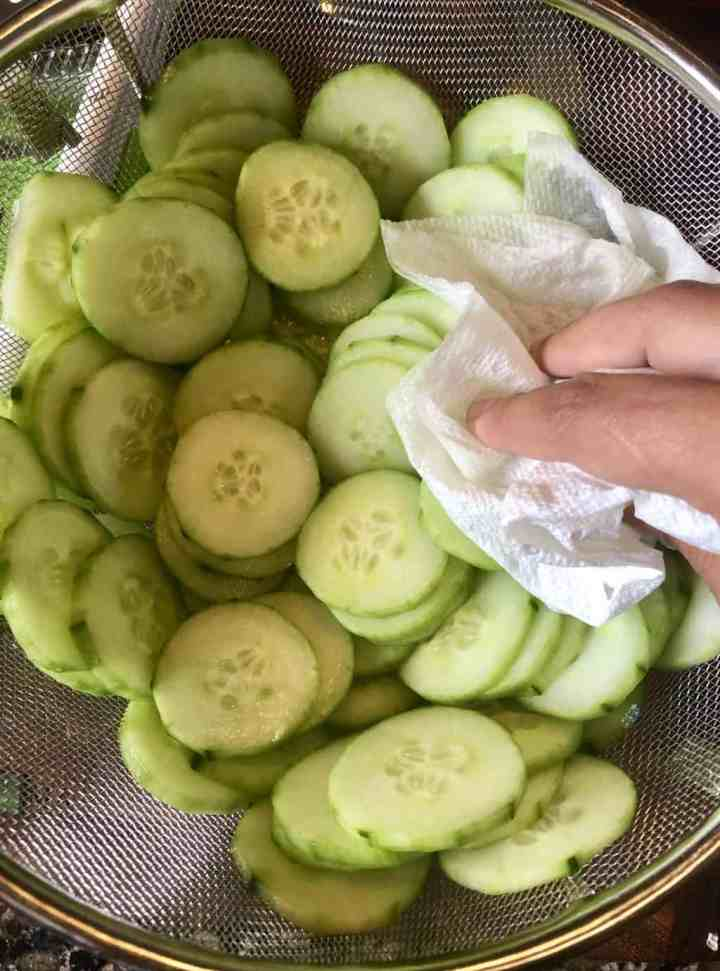 sliced cucumbers in a colander being pat dry with a paper towel