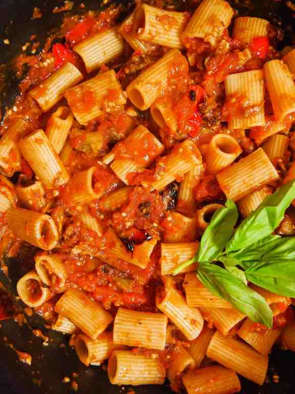 roasted eggplant, bell peppers, rigatoni pasta, and red sauce in a dutch oven with fresh basil leaves