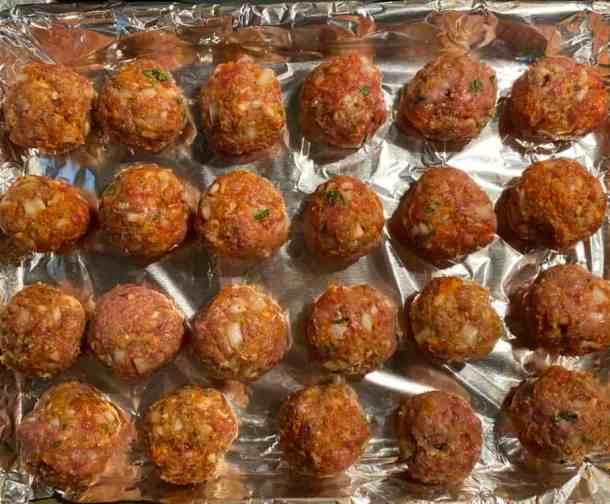 formed meatballs on a baking sheet on foil pre cook