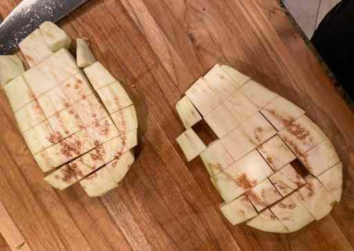 two eggplant steaks on a wooden cutting board diced
