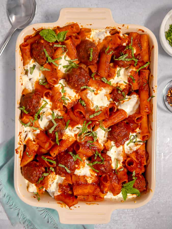 overhead shot of meatball pasta casserole in a baking dish with a blue napkin and silver spoon