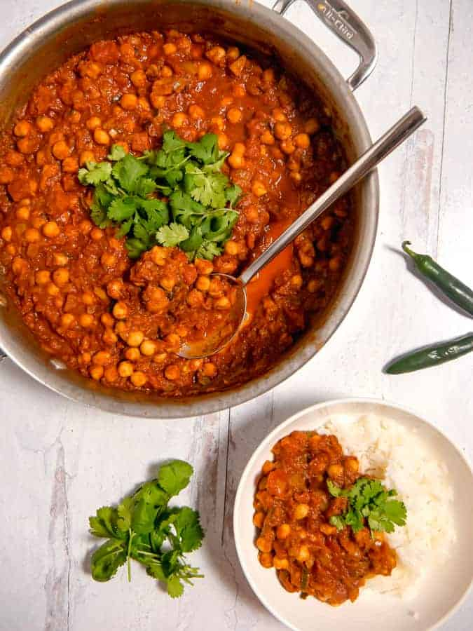 Overhead photo of a skillet with chickpea masala and a bowl of rice