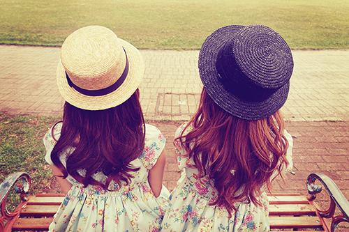 「ベンチ」「公園」「友達」「双子ルック」「女性・女の子」「巻き髪」「帽子」「春」などがテーマのフリー写真画像
