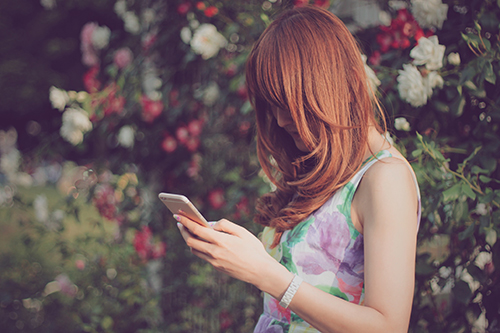 「iPhone」「スマートフォン」「スマホ」「公園」「女性・女の子」「巻き髪」「春」「花」などがテーマのフリー写真画像
