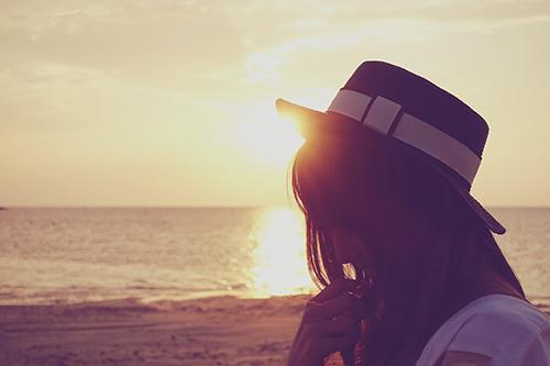 「シルエット」「夏」「夏の夕暮れ」「夕陽」「女性・女の子」「巻き髪」「帽子」「海」などがテーマのフリー写真画像