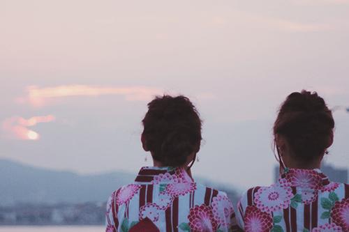 浴衣で肩を並べて夕焼けを眺める双子の女の子