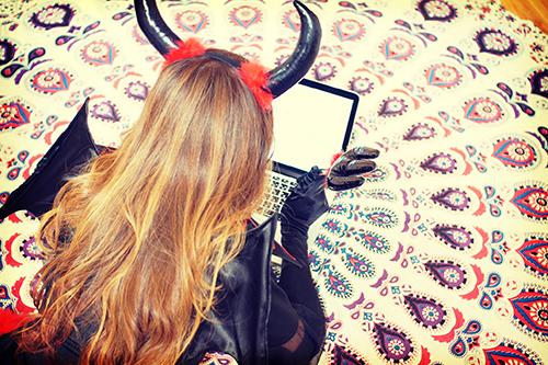 フリー写真素材:パソコンで何のイタズラをしようか考え中のデビルな女の子