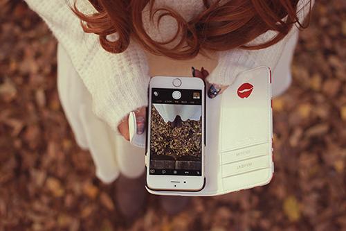 iPhoneでイチョウを踏みしめる足元を撮影する女の子