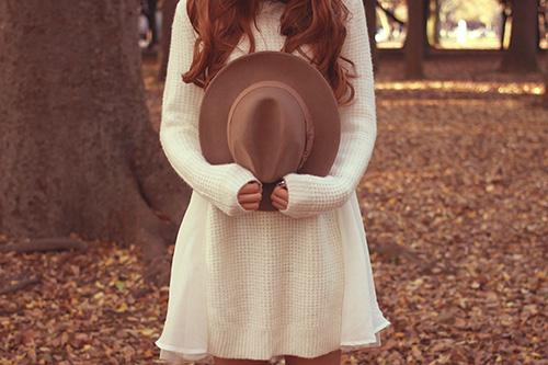 森の中で帽子を抱えて立っている女の子