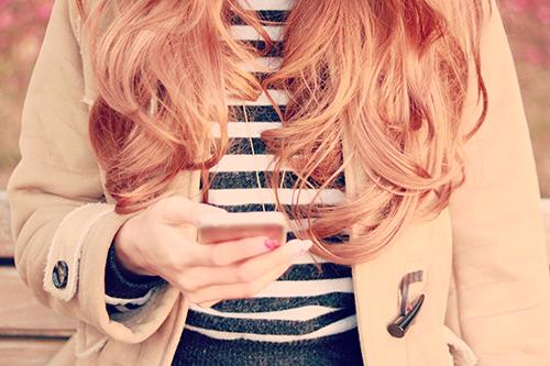 冬の公園でスマートフォンを操作している女の子