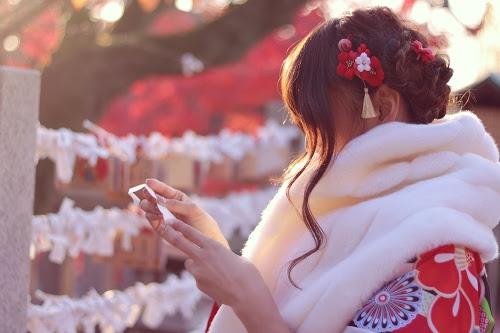 初詣で引いたおみくじをじっくり読んでいる着物の女の子