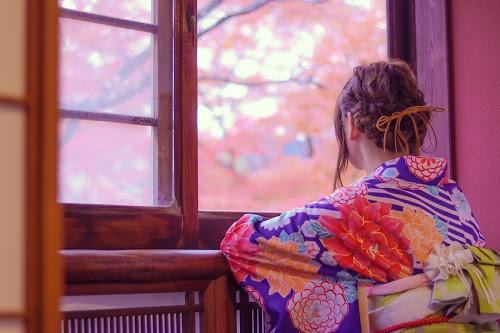 窓から美しい紅葉を眺める着物の女の子