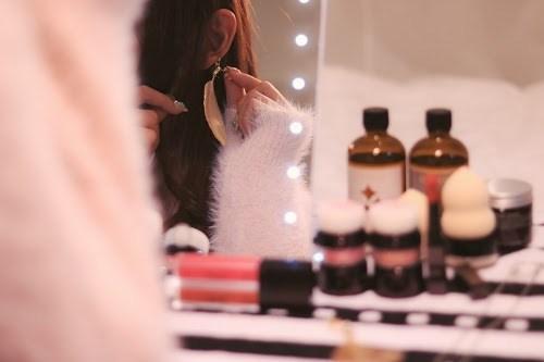 鏡を見ながらイヤリングをつけている女の子
