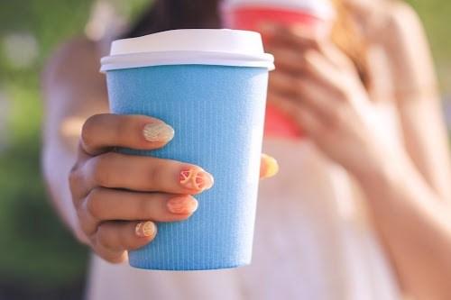 ホットコーヒーを差し出す女の子