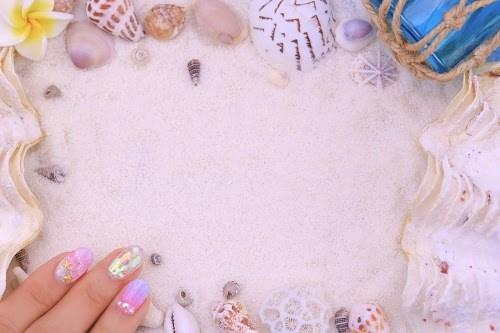 砂浜の上に作った貝殻のフレームと夏ネイル