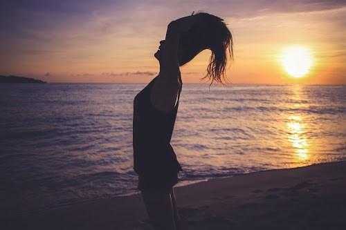 海へと沈む夕日をバッグにシャンプーのCMぽいポーズをしている女の子