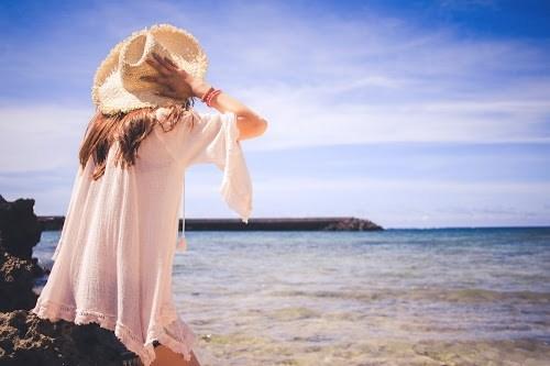 海で風に飛ばされそうな帽子をギュッと押さえて座っている女の子