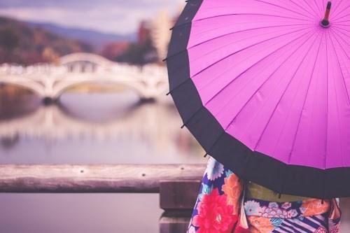 雨の日に橋の上から金沢の景色を眺める和服姿の女の子