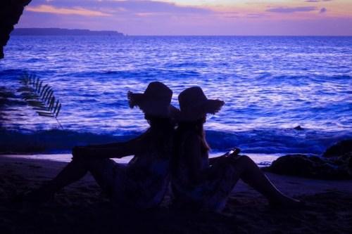 日が沈んでいくビーチで背中合わせに座る双子の女の子たち at 砂山ビーチ
