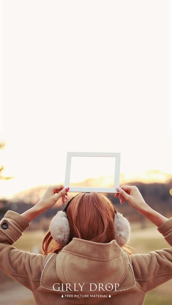 おしゃれなフリーのスマホ壁紙(待受け):【オシャレなiPhone壁紙】冬の夕焼けの中でフレームを持った女の子