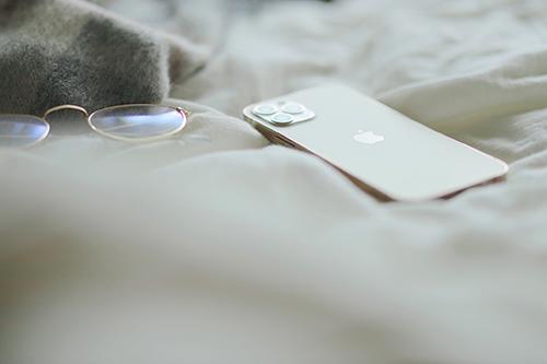 フリー写真素材:ベッドの上に無造作に置かれたiPhone 12 Pro(Gold)