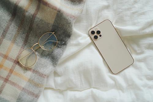 フリー写真素材:冬のベッドとiPhone 12 Pro(Gold)