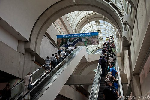 """A banner for the conference theme """"Understanding Our World"""" hangs in the San Diego Convention Center as attendees use escalators."""
