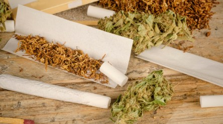 Ingredients to roll a joint on a rustic wooden table
