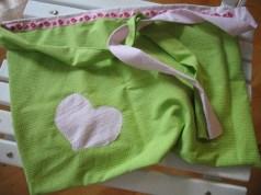 """Forklæde til lille pige. """"Forsiden"""" i æblegrønt babytern. Bemærk det dekorative bånd foroven."""
