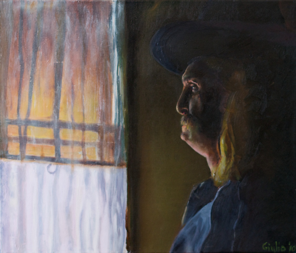Man in hat standing, looking out a sunlit curtained window with yellow shade half-drawn