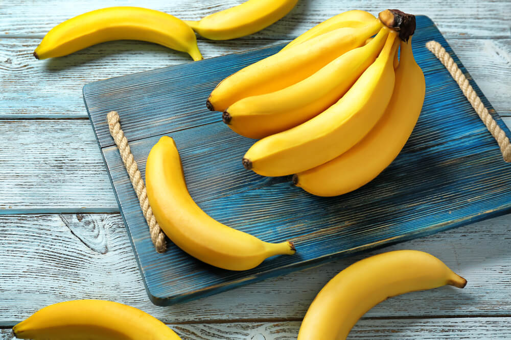 Bananas on a wood cutting board and table