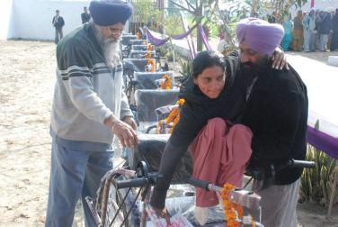Ein Vater hebt seine Tochter in ihr neues Dreirad.