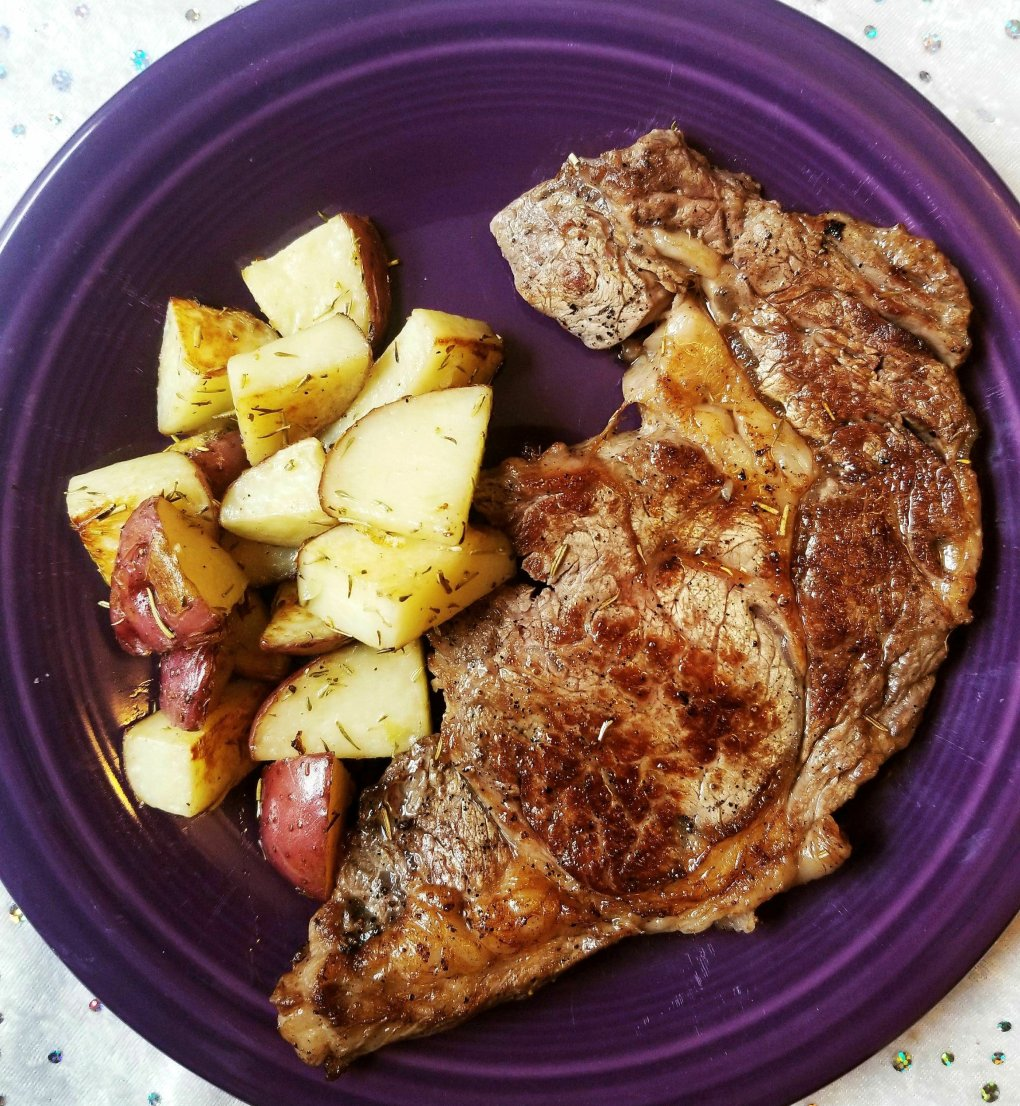 Ribeye steak with herbed ghee (garlic, rosemary, and thyme) and roasted red skin potatoes