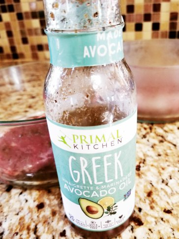 Primal Kitchen Greek Vinaigrette & Marinade (Avocado Oil) and two strip steaks marinating