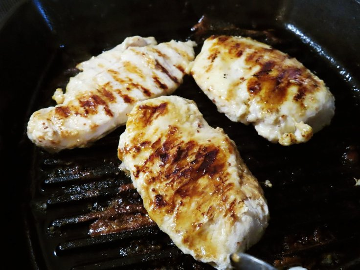 Primal Kitchen Honey Mustard Chicken grilling on a Lodge cast iron grill pan