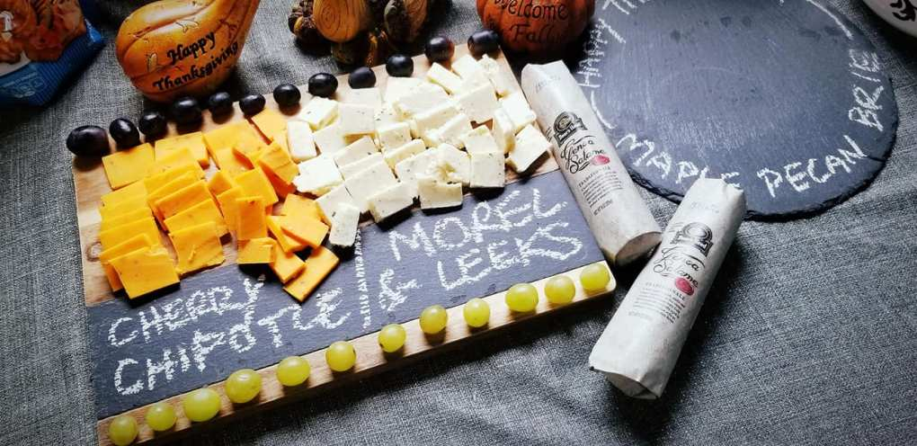 A couple of different cheeses on the cheeseboard
