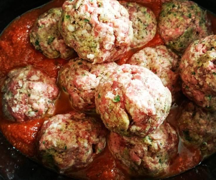 Huge mozzarella stuffed meatballs simmering in the slow-cooker