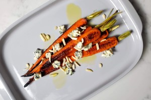 Carrots Roasted in Duck Fat on a Platter with olive oil, blue cheese and almonds