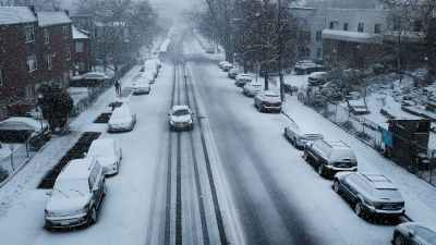 Rua coberta de neve enquanto carro anda pela via