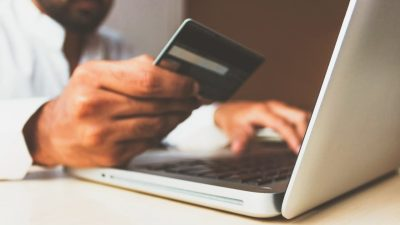 pessoa segura cartão de crédito enquanto usa o computador