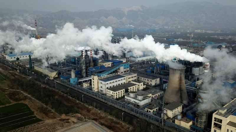 Imagem aérea de indústrias emitindo uma fumaça branca e espessa.